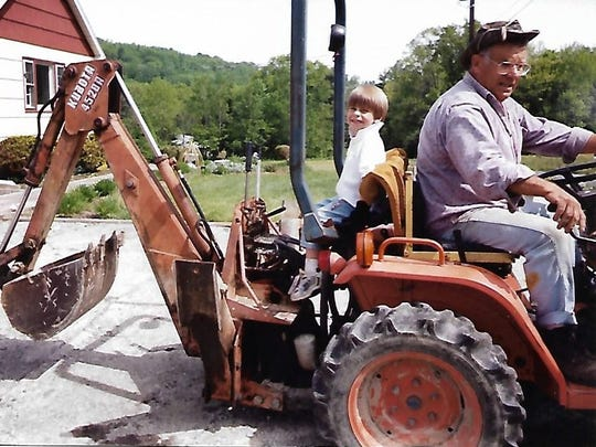John Stanchak drives while his son, Kyle, works the