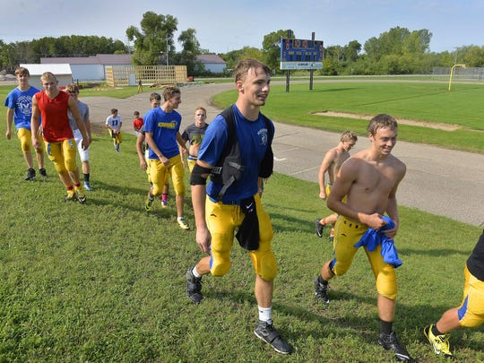 Kimball football players walk off the field during a break in practice Monday at the school. The school has mostly recovered after the football field, goalposts, an outbuilding, and some equipment were damaged during a brief tornado touchdown May 16.