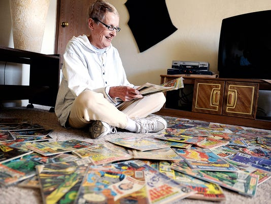 Judy Dette smiles while looking at her collection of comics on Friday at her home on Mesilla Drive in Aztec.