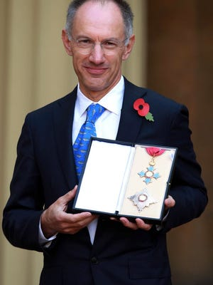 Michael Moritz, chairman of Sequoia Capital, poses for pictures with his Honour of Knighthood medal after receiving it during an investiture ceremony at Buckingham Palace in London in 2013.