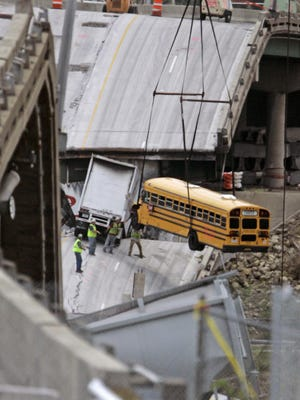 In this Aug. 12, 2007 file photo, workers remove a school bus from the interstate 35W bridge collapse site in Minneapolis. The school bus was carrying 52 children from a visit to a water park when it dropped with the bridge during the collapse. All the children survived the fall. According to court testimony in a federal terrorism trial, Mohamed Roble, who was one of the passengers on the bus, is now believed to be in Syria with the Islamic State group.