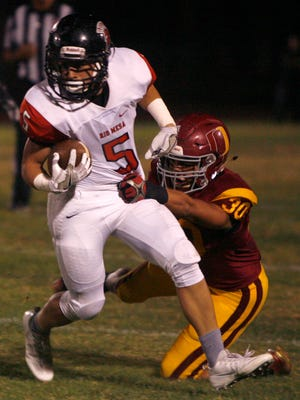 Rio Mesa High running back Isaac Aguilera (left) just escapes the tackle of Oxnard linebacker Eduardo Cardenas during Friday night's game.