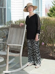 Marjorie Mounts wears a black silk tunic with three-quarter length sleeves with silk black-and-white patterned pants by AGB; Nickel's open-toed black-and-white patent shoes; and a natural straw hat with black fabric flower trim.