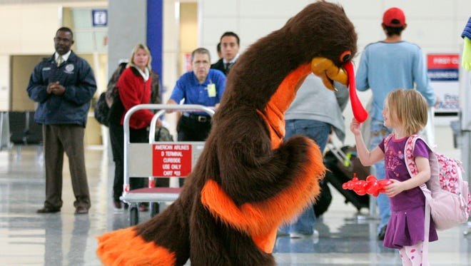 In this Wednesday, Nov. 26, 2008, file photo, Abby Harris, 4, says hello to a turkey greeting passengers at Dallas-Fort Worth International Airport.