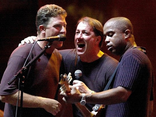 Dan Marino, left, Jim Kelly and the lead singer for Hootie and the Blowfish, Darius Rucker, sing during a tribute to Marino on Aug. 23, 2000 at Pro Player Stadium in Miami.