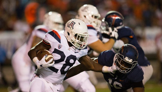 Arizona running back Nick Wilson (28) tries to break a tackle from UTEP linebacker Alvin Jones (16) during the first quarter at the Sun Bowl.