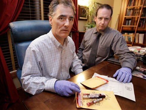 Cook County Sheriff Tom Dart, left, and sheriff's detective Jason Moran are photographed with three recently discovered vials of mass murderer John Wayne Gacy's blood.