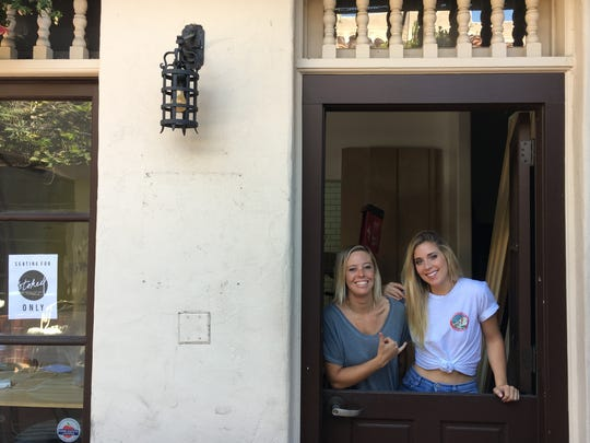 Stoked Coffee Co. & Acai Bowls co-owners Aubrey Rasmussen, left, and Cammy Morrell take a break from construction to pose in the cafe's doorway in downtown Ventura.