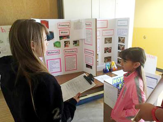 """Judge Alexis Madrid questions third-grader Isenya Silva about her project titled """"Freezing Water."""""""