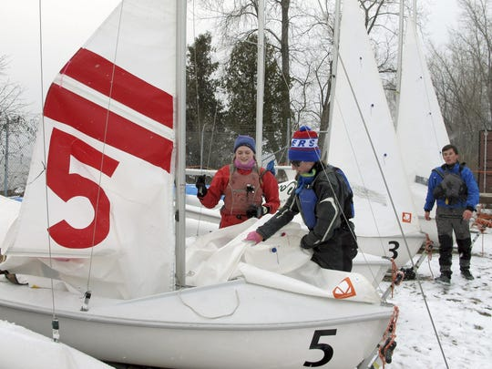 Sailing team members Lilla Salvesen, left, and Lindsay Doyle attach sails to a boat while Will Crary, right, prepares another boat behind them on the shore of Lake Champlain.