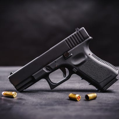 A black 9mm pistol on a black wooden table.