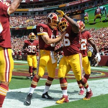 Sep 14, 2014; Landover, MD, USA; Washington Redskins fullback Darrel Young (36) is congratulated by quarterback Kirk Cousins (8) after scoring a touchdown against the Jacksonville Jaguars during the first half at FedEx Field. Mandatory Credit: Brad Mills-USA TODAY Sports