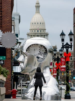 """Katie Smith looks at the large new sculpture on Friday, Dec. 8, 2017, that was installed at the intersection of Michigan Avenue and Museum Drive in Lansing. The work, titled """"Portrait of a Dreamer,"""" was created by St. Johns artist Ivan Iler. The large bust features a crank that when turned moves gears that protrude from the forehead of the figure. According to a Facebook post on the City of Lansing's page, a ribbon cutting ceremony and press conference is scheduled for Monday, December 11, 2017, at 2:30 p.m."""
