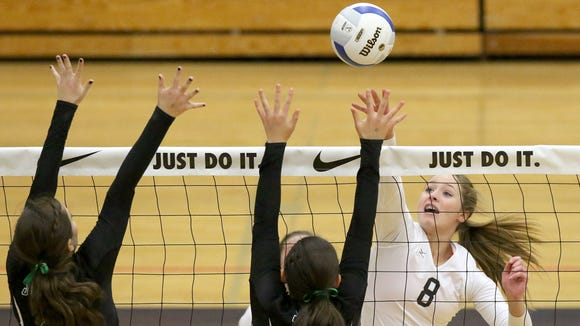 Silverton High School's Maggie Buchholz (8) goes up for a kill but is blocked by Summit defenders during the 2015 state volleyball tournament.