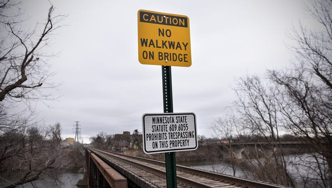 A sign is posted at the west entrance to the railroad bridge over the Mississippi River near Veterans Bridge Thursday, March 30, in St. Cloud.