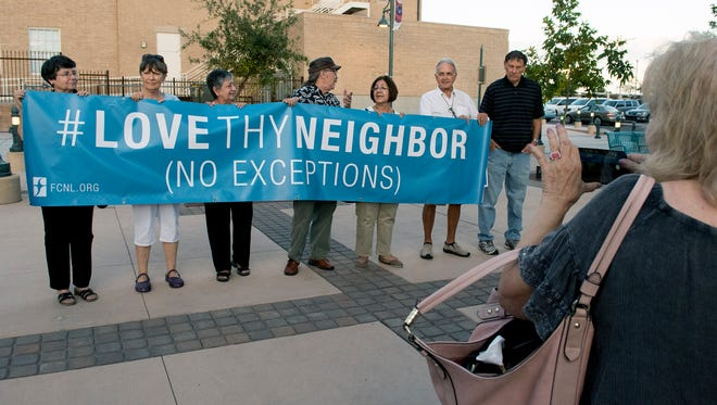 "A group displays a sign, ""Love thy neighbor, no exceptions"" during a vigil Sunday, Aug. 13, 2017, at Plaza de Las Cruces against the hate, violence and racism that erupted the previous day in Charlottesville, Virginia."