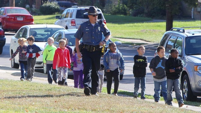 Green Township police Lt. Jim Vetter walks along Sidney Road with students returning to Covedale School after it was evacuated due to a bomb threat.
