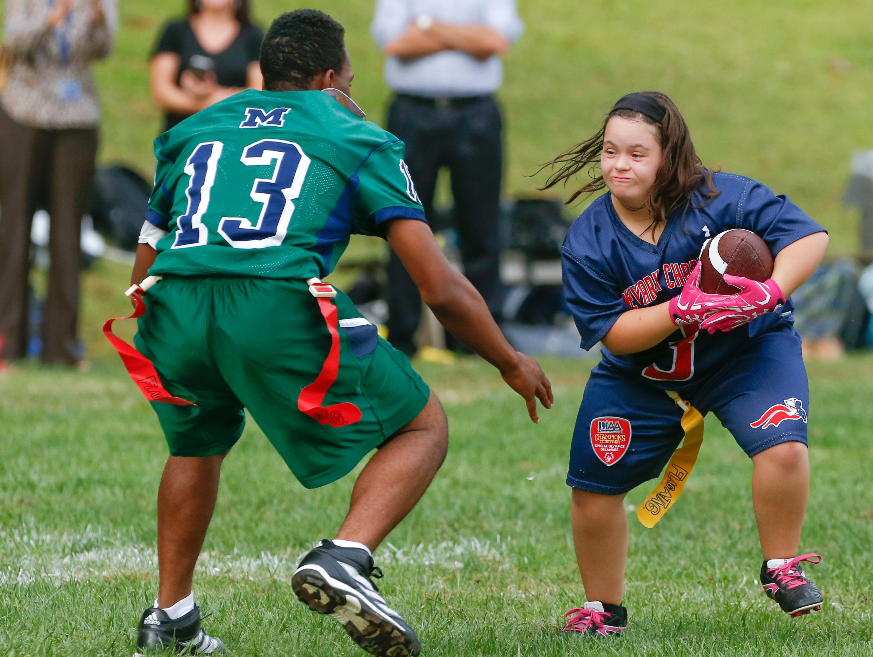 McKean's Da'Quan Scott defends as Newark Charter's Hannah Tressler looks for running room in McKean's 24-14 win in the Unified flag football opener at McKean High School Tuesday.