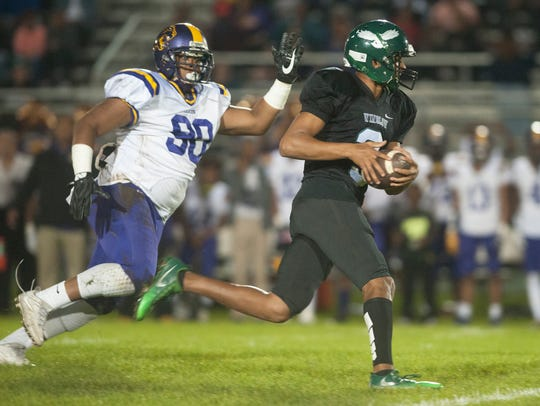 Winslow Township's Prince-Dru Bey runs the ball past Camden's Christopher Levy during a 2017 football game played at Winslow Township High School.