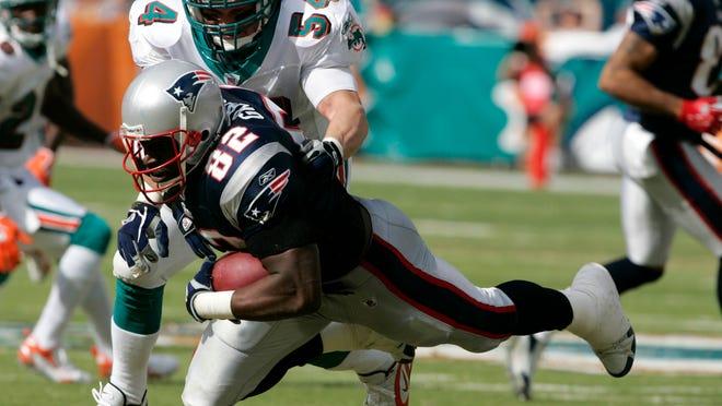 Dolphins linebacker Zach Thomas stops Patriots tight end Daniel Graham in 2006.
