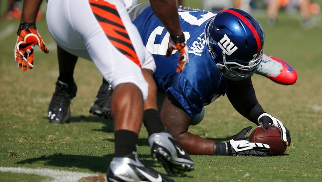 New York Giants defensive tackle Dominque Hamilton falls on a fumble by Cincinnati Bengals running back Cedric Peerman during Cincinnati Bengals training camp Tuesday on the practice fields adjacent to Paul Brown Stadium.