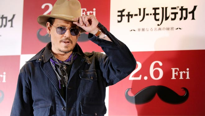 Johnny Depp tips his hat to Tokyo photographers on Wednesday.