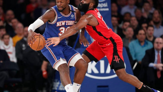 Houston Rockets guard James Harden, right, tries to tip the ball away from New York Knicks forward Julius Randle (30) beneath the Knicks' basket during the first quarter of an NBA basketball game in New York, Monday, March 2, 2020.
