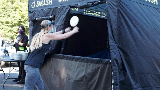 Salve Regina sophomore Hannah Rossman smashes her plate at the Rage Room event on Saturday.