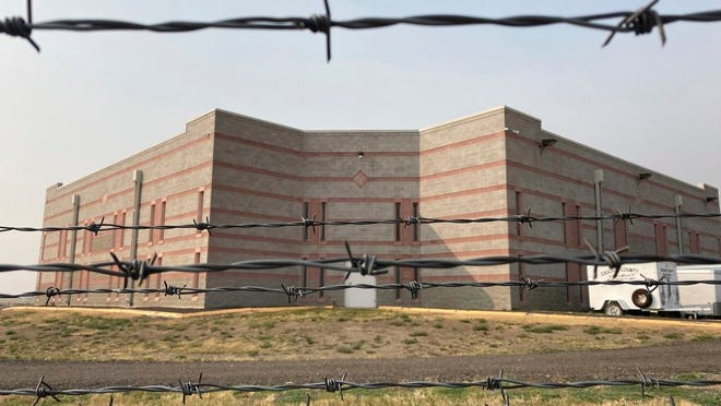 In this Sept. 18, 2020 photo, the Cascade County Detention Center is seen through barbed wire fencing in Great Falls, Mont. The jail is one of three in Montana experiencing COVID-19 outbreaks, which Sheriff Jesse Slaughter blames on overcrowding and too many inmates awaiting transfer to the state prison.
