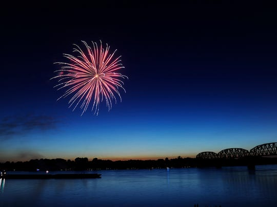 Fireworks explode over the Ohio River on the Henderson