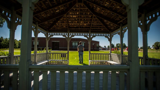 Essex Elementary School Principal Peter Farrell looks out over the grounds of a very different place from 10 years ago. Farrell wasn't here back then, but the signs of healing -- like the gazebo outside dedicated to teacher Alicia Shanks -- are a quiet reminder of how the school has overcome.