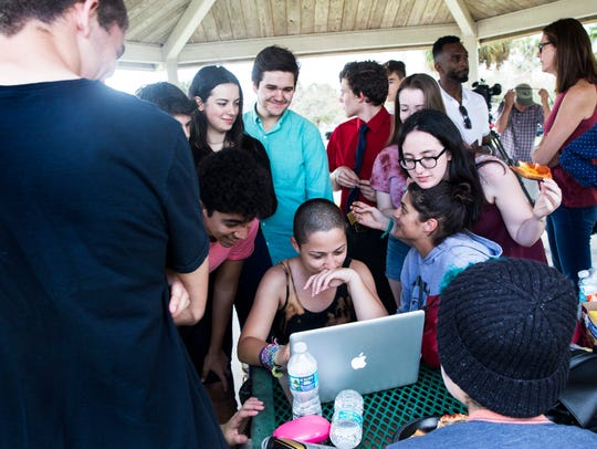 Emma Gonzalez, 18, center, a senior at Marjory Stoneman Douglas High School, is surrounded by friends as she answers a social media message from actress and singer Zendaya at North Community Park on Feb. 18, 2018, in Coral Springs, Fla.