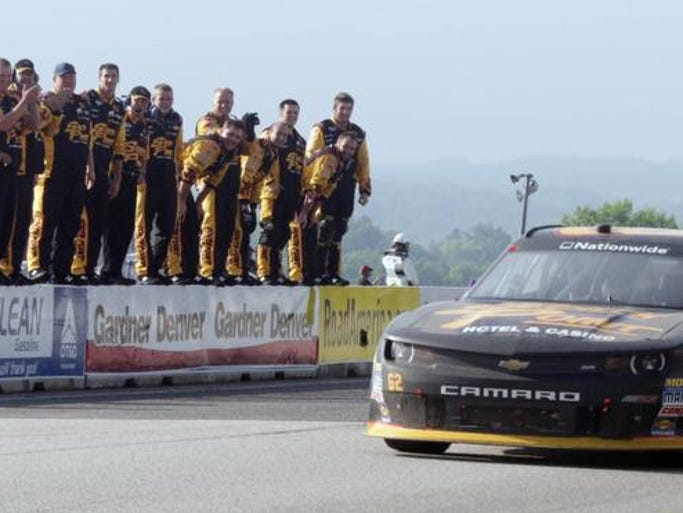 Brendan Gaughan's pit crew stands on a wall while he motors in after his victory in the Gardner Denver 200 Saturday June 21, 2014 at Elkhart Lake's Road America.