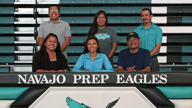 Navajo Prep's Sarah Chacon, bottom row at center, signs her national letter of intent on Monday at the Eagle's Nest in Farmington, surrounded by her parents and her track and cross-country coaches. Chacon will compete in both sports at Fort Lewis College in Durango, Colo.