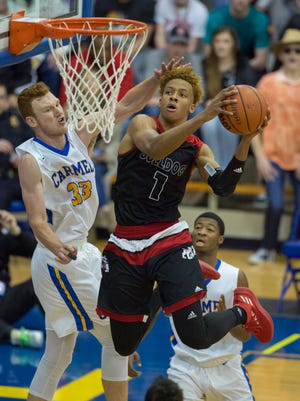 New Albany High School senior Romeo Langford (1) takes the ball to the basket as he's defended by Carmel High School junior John Michael Mulloy (33) during the second half an IHSAA varsity basketball game at Carmel High School, Saturday, December 16, 2017. New Albany won 59-48.