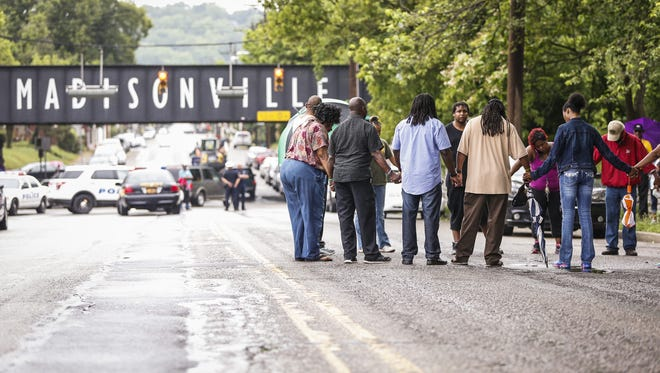 Community members gather in a circle to mourn at the scene of Friday's shooting in Madisonville.