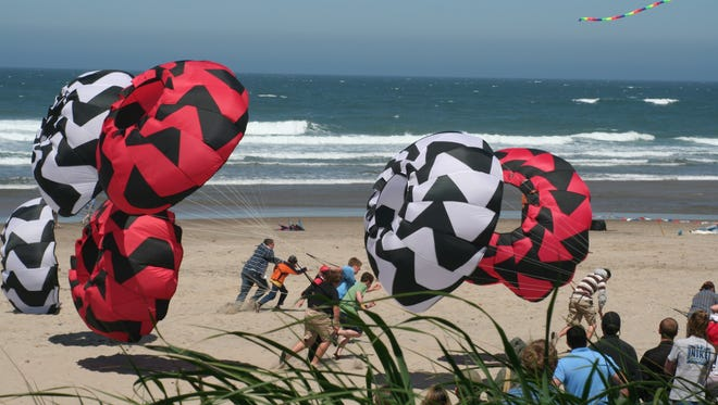 """Visitors to Lincoln City's Fall Kite Festival can compete for free in the """"Running of the Bols,"""" which has people attached to kites running into the wind."""