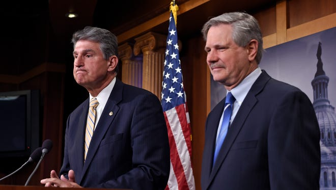 Sen. Joe Manchin, D-W.Va., left, and Sen. John Hoeven, R-N.D., right, listens to a reporter's question during a news conference on Capitol Hill in Washington, Tuesday, Jan. 6, 2015, where they discussed  their plan to introduce legislation to approve the Keystone XL pipeline project. (AP Photo/Susan Walsh)