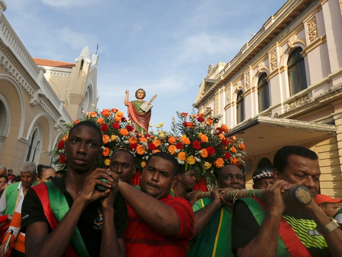 Worshipers carry a stutue in the procession of Saint