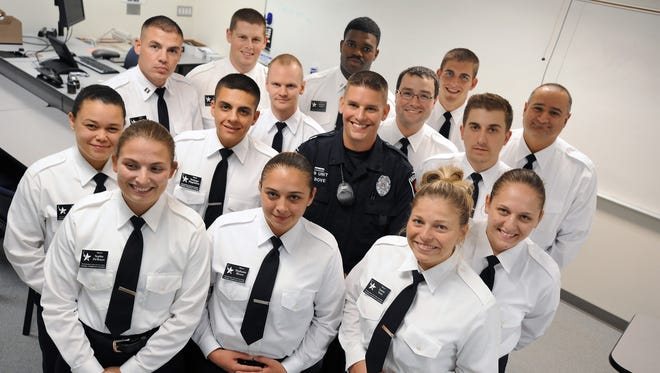 East Lansing Police Officer Travis Bove, center, poses with most of the group who recently helped him of the 15 Lansing Community College Police Academy students  after their classes at the school Thursday 9/24/2015.  The group of students physically moved a vehicle off Bove when he was pinned between a police vehicle and large recreational vehicle after an accident at a  Law Enforcement Torch Run for Special Olympics event in East Lansing.