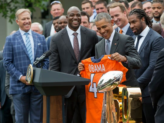 President Barack Obama holds up a Denver Broncos team football jersey, as he welcomes the Super Bowl 50 champions during a ceremony in the Rose Garden of the White House in Washington on Monday, June 6, 2016. A federal lawsuit filed by the Caledonian Record of St. Johnsbury accuses the Newport Daily Express of improperly downloading and publishing an Associated Press photograph from this event.