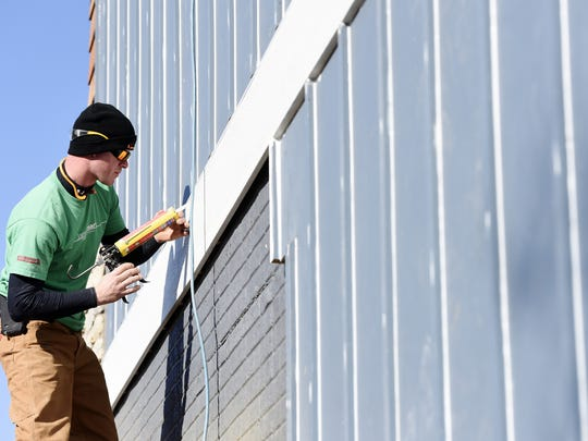 Brandon Johnston, framing foreman at Jarrod Smart Construction pcaulks joints and nail holes on a custom home under construction in Arbor's Edge in eastern Sioux Falls, April 13, 2016.