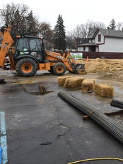 Some bales of straw, rebar and a backhoe are signs