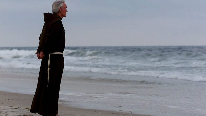 Father Mychal Judge, who was the New York City Fire Department chaplain, stands at the shore before a service where candles were lit for the victims of TWA Flight 800, July 17, 2000, at Smith Point Park in Shirley, N.Y. Father Mike, rushing to comfort victims of the World Trade Center terrorist attack, was among the first to die as he was hit by a falling chunk of debris on Sept. 11, 2001.