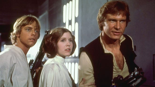 "Mark Hamill, left, Carrie Fisher, center, and Harrison Ford, right, are shown in a scene from the 1977 film ""Star Wars."""