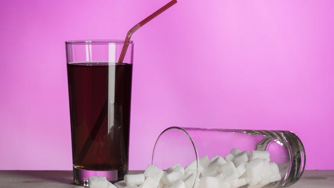 Glass of cola and another full of sugar on the side. Representing how much sugar can be in cola drinks.
