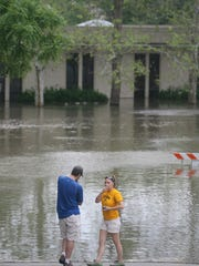 Onlookers view the rising floodwater surrounding the