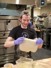 Michael Kinney stretches pizza dough at Owensboro's