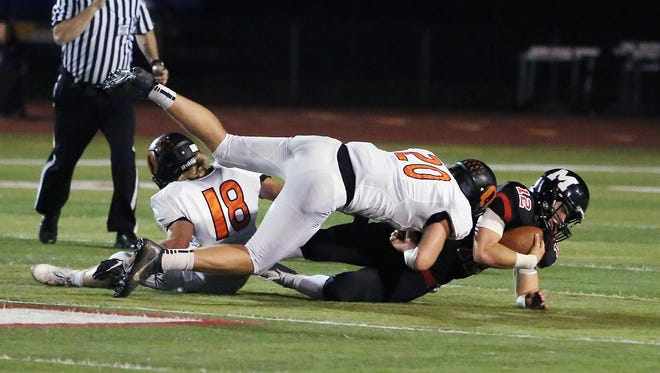Sprague's Dane McKinney (No. 18) and Teagan Quitoriano take down McMinnville's Wyatt Smith as the Olys defeat the Grizzlies 49-27 in Greater Valley Conference game on Friday, Sept. 23, 2016, in McMinnville.