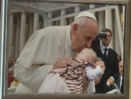 A portrait of Pope Francis kissing Ave hangs in the